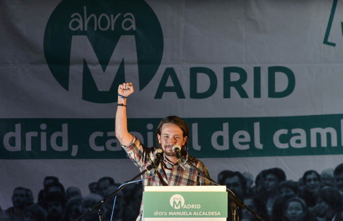 """Spanish Euro Deputy and leader of left-wing party Podemos Pablo Iglesias raises his fist during a press conference following the results in Spain's municipal and regional elections in Madrid on May 24, 2015.  Spain's """"Indignado"""" protest movement gave its ruling conservative rivals a battering in local elections Sunday, topping the vote for mayor in Barcelona and shattering the ruling party's majority in Madrid.     AFP PHOTO / PEDRO ARMESTRE"""