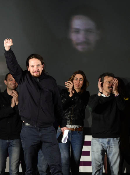 "Anti-austerity party Podemos' leader Pablo Iglesias (L) raises his fist next to candidate for Madrid's regional presidency Jose Manuel Lopez (R) as they meet with supporters following the results in Spain's municipal and regional elections in Madrid on May 24, 2015. Spain's ""Indignado"" protest movement gave its ruling conservative rivals a battering in local elections today, topping the vote for mayor in Barcelona and shattering the ruling party's majority in Madrid.   AFP PHOTO / GERARD JULIEN"