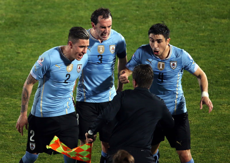 (L to R) Uruguay's defender Jose Maria Gimenez, Uruguay's defender Diego Godin and Uruguay's midfielder Jorge Fucile argue with the linesman during their 2015 Copa America football championship quarterfinal match, in Santiago, on June 24, 2015.     AFP PHOTO / CLAUDIO REYES