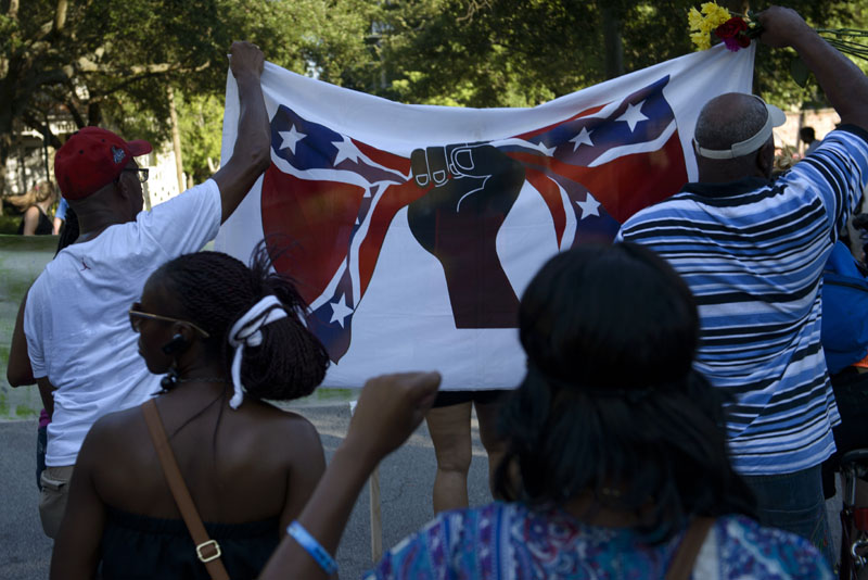 """People march through neighborhood streets during a protest June 20, 2015 in Charleston, South Carolina. The group gathered to protest violence and discrimination against African Americans as well as the mass shooting at the Emanuel AME Church. A website apparently created by Dylann Roof emerged Saturday in which the accused Charleston church shooter rails against African Americans and appears in photographs with guns and burning the US flag. His arrest warrant revealed how on June 17 he allegedly shot the six women and three men, aged 26 through 87, multiple times with a high-caliber handgun and then stood over a survivor to make a """"racially inflammatory"""" statement.     AFP PHOTO/BRENDAN SMIALOWSKI"""