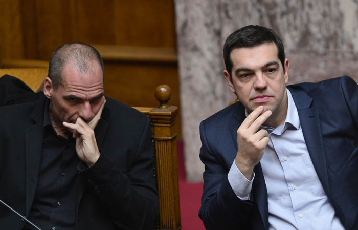 Greek Prime Minister Alexis Tsipras (R) sits next to Finance Minister Yianis Varoufakis during the vote for the president, at the Greek parliament in Athens, on February 18, 2015.  Greece's parliament elected pro-European conservative Prokopis Pavlopoulos as the country's new president, a move calculated to bolster the hard-left government in its critical EU bailout talks. AFP PHOTO / LOUISA GOULIAMAKI