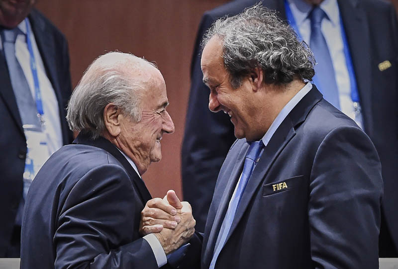 TOPSHOTS FIFA President Sepp Blatter (Foreground-L) shakes hands with UEFA president Michel Platini after being re-elected following a vote to decide on the FIFA presidency in Zurich on May 29, 2015. Sepp Blatter won the FIFA presidency for a fifth time after his challenger Prince Ali bin al Hussein withdrew just before a scheduled second round. AFP PHOTO / MICHAEL BUHOLZER