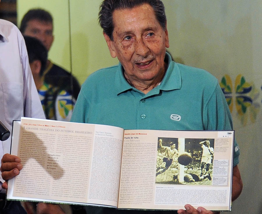 "Uruguayan former footballer, Alcides Ghiggia, 83, shows a book given as a gift by the Secretary of Tourism of Brazil, Marcia Lins, before leaving his footprints at Maracana's Walk Of Fame, in Rio de Janeiro on December 29, 2009. Ghiggia was honoured for his famous goal which gave Uruguay the 2-1 victory over Brazil in the final of the 1950 FIFA World Cup and crowned them champions. ""Only three people managed to silence the Maracana Stadium: the Pope, Frank Sinatra and I"", once sentenced the eighty-three-year-old in reference to that goal.  AFP PHOTO/VANDERLEI ALMEIDA"