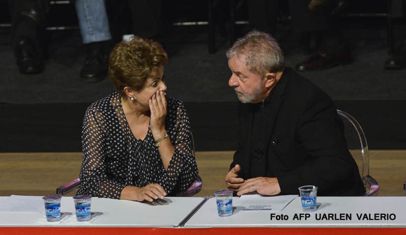 Brazilian President Dilma Rousseff (L) and former Brazilian president Luiz Inacio Lula da Silva talk during the celebration of the 35th anniversary of the Workers' Party (PT) in Belo Horizonte, Brazil on February 6, 2015. AFP PHOTO / Uarlen VALERIO