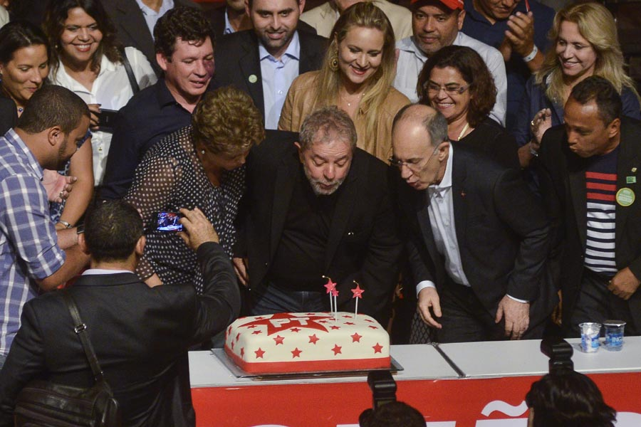 Brazilian president Dilma Rousseff  (L) and former president Luiz Inacio Lula da Silva blow the cake's candles during the celebration of the 35th anniversary of the Workers' Party (PT) in Belo Horizonte, Brazil on February 6, 2015. Attends (top-L) Joao Vaccari Neto, PT treasurer. AFP PHOTO / Uarlen VALERIO