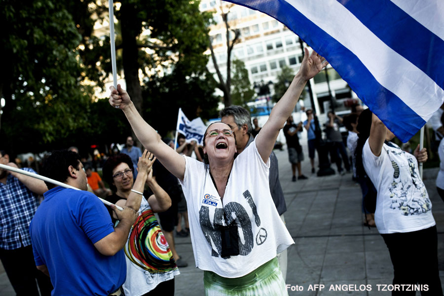 A woman celebrates at Syntagma Square in Athens on July 5, 2015 after the first exit-polls of a referendum on austerity measures. A referendum to decide whether or not Greece will accept the bailout conditions proposed jointly by the European Commission, the International Monetary Fund and the European Central Bank will take place on July 5. AFP PHOTO / Angelos Tzortzinis