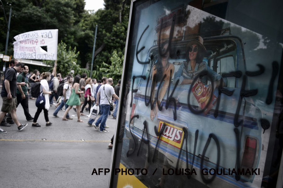 "Protesters march past a bus stop sprayed with anti-EU graffiti during a demonstration calling for an exit from the eurozone and a ""No"" vote in the upcoming referendum in Athens on June 28, 2015. Greece weighed drastic banking restrictions to stave off a financial collapse as anxious Greeks emptied cash machines amid fears that banks will be closed this week. AFP PHOTO / LOUISA GOULIAMAKI"