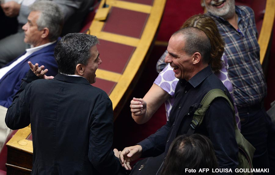 Former Greek Finance minister Yianis Varoufakis jokes with Finance Minister Euclid Tsakalotos (L) during a session at the Greek parliament prior the vote in Athens on July 22, 2015. Prime Minister Alexis Tsipras faced a new test of his authority in parliament on July 22, where MPs were to vote on a second batch of reforms to help unlock a bailout for Greece's stricken economy. The embattled premier last week faced a revolt by a fifth of the lawmakers in his radical-left Syriza party over changes to taxes, pensions and labour rules demanded by EU-IMF creditors. AFP PHOTO/ LOUISA GOULIAMAKI