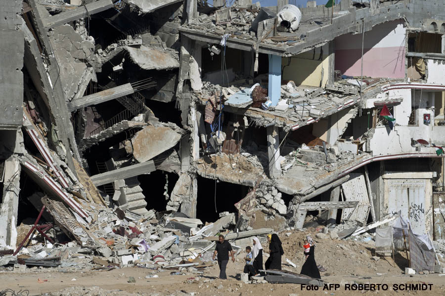 A Palestinian family walks on August 27, 2014 past the collapsed remains of a building that was destroyed in fighting between Hamas militants and Israel during 50 days of fighting in Shejaiya. Israel and Palestinians both boasted of victory in the Gaza war but analysts say Hamas received only promises while the conflict aggravated divisions in the Israeli leadership.  AFP PHOTO/ROBERTO SCHMIDT