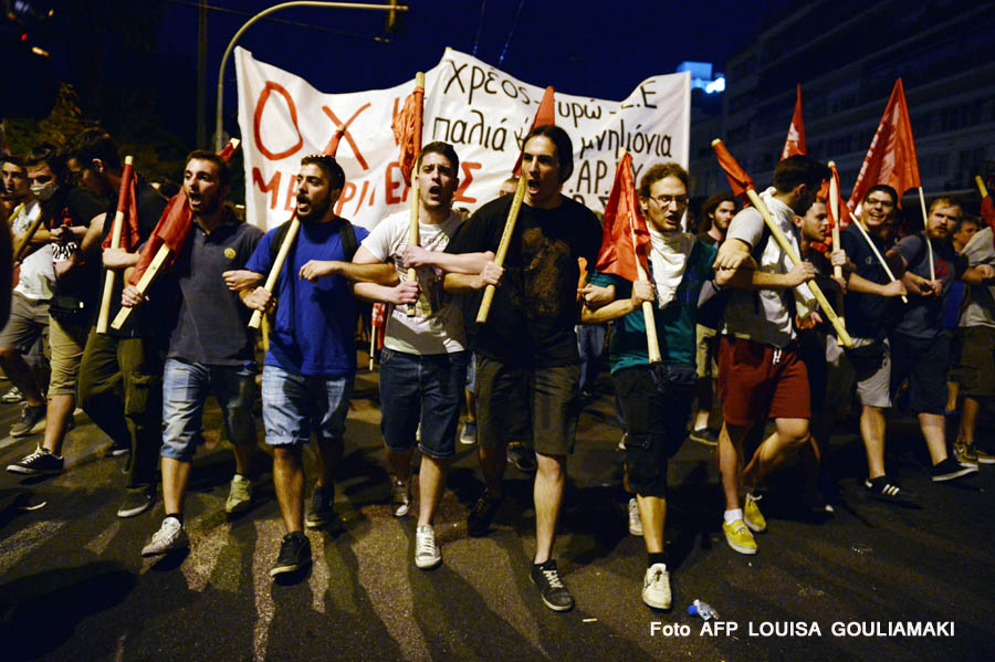 Protesters march, holding banners and flags in front of the Greek parliament in Athens during an anti-austerity protest on July 15, 2015. Anti-austerity protesters hurled petrol bombs at police in front of Greece's parliament on July 15 as lawmakers began debating deeply unpopular reforms needed to unlock a new eurozone bailout.Riot police responded with tear gas against dozens of hooded protesters who set ablaze parts of Syntagma square in central Athens. AFP PHOTO/ LOUISA GOULIAMAKI