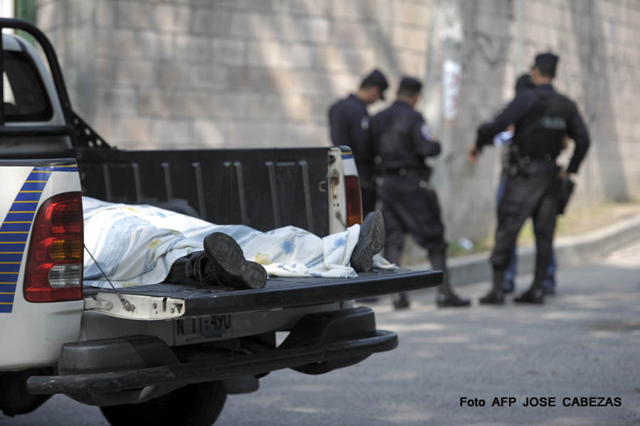 Policemen stand by the body of Edgar Sibrian Tobar, a truck driver killed when he was driving his children to school, in San Salvador on May 12, 2011. More than 10 people are killed every day in El Salvador, according to  National Civil Police statistics.  AFP PHOTO/JOSE CABEZAS