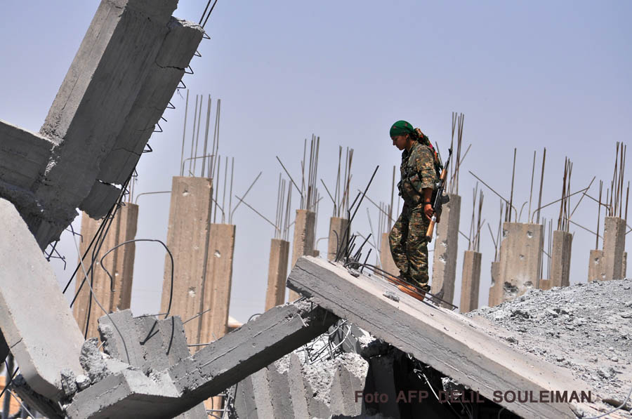 A female fighter from the Kurdish People Protection Unit (YPG) looks at destruction in the Syrian town of Ain Issi, some 50 kilometres north of Raqqa, the self-proclaimed capital of the Islamic State (IS) group during clashes between IS group jihadists and YPG fighters on July 10, 2015. AFP PHOTO / DELIL SOULEIMAN