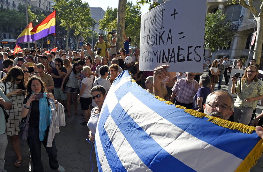 """Protesters wave a Greek flag and hold a placard reading """"IMF+Troika=Criminals"""" as they protest in front of the European Commission headquarters in Barcelona during a demonstration in support of Greece, on June 29, 2015. Greece blindsided creditors on June 27, 2015 by calling a referendum for July 5 on the latest bailout proposal being offered to Greece, a move interpreted by its creditors as Athens' desire to break off negotiations. AFP PHOTO / LLUIS GENE"""