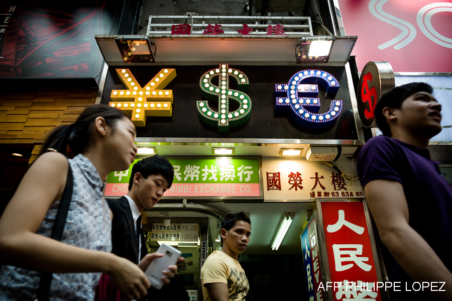 In this picture taken on October 25, 2013 pedestrians walk past a money exchange booth in Hong Kong. The US Treasury said on October 30, 2013 that the Chinese yuan remains undervalued despite its significant appreciation in 2013 and called on Beijing to disclose more about its market intervention. AFP PHOTO / Philippe Lopez