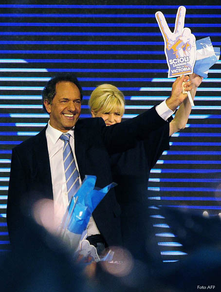 "Buenos Aires province Governor and elected presidential candidate for the ""Frente para la Victoria"" ruling party, Daniel Scioli (L) and his wife wave to supporters  Alzua after receiving most votes in the national primary elections in Buenos Aires on August 10, 2015 ahead the general elections to be held on October 25th. Argentines voted Sunday in presidential primaries seen as an early indicator of who is best positioned to succeed President Cristina Kirchner. AFP PHOTO / TELAM / MAXIMILIANO LUNA    == RESTRICTED TO EDITORIAL USE / MANDATORY CREDIT ""AFP PHOTO / TELAM / MAXIMILIANO LUNA"" /  NO MARKETING / NO ADVERTISING CAMPAIGNS /  DISTRIBUTED AS A SERVICE TO CLIENTS =="
