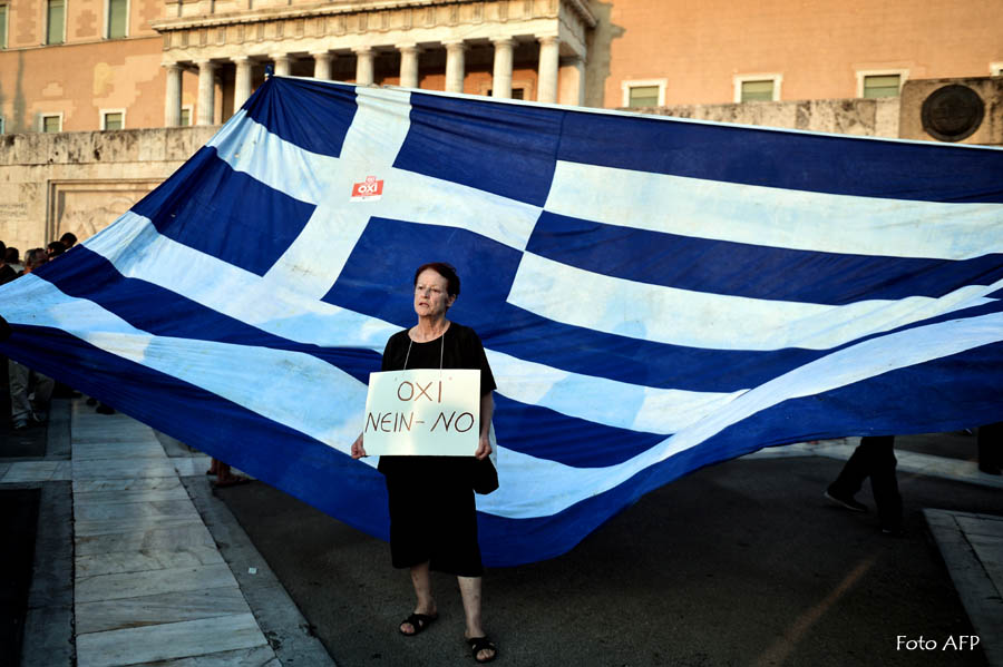 """A woman holds a plackard reading supporting a """"No"""" vote in the forthcoming referendum on bailout conditions set by the country's creditors, in front of a huge Greek flag outside the Greek parliament in Athens, on June 29, 2015.  Some 17,000 people took to the streets of Athens and Thessalonique to say 'No' to the latest offer of a bailout deal Monday, accusing Greece's international creditors of blackmail. AFP PHOTO / LOUISA GOULIAMAKI"""