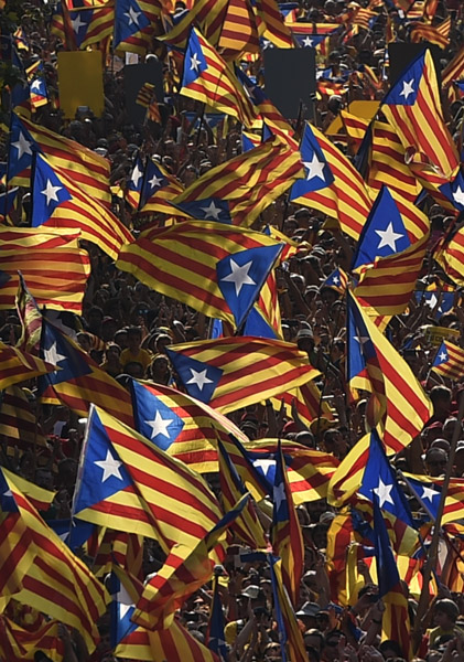 """Catalans hold Catalan independentist flags (Estelada) during celebrations of Catalonia National Day (Diada) in Barcelona on September 11, 2014. Red and yellow flags filled the streets of Barcelona today as Catalan nationalists fired up by Scotland's independence referendum rallied to demand a vote on breaking away from Spain. Demonstrators planned to mass in the late afternoon along two central Barcelona avenues in the shape of a giant letter """"V"""" for vote.    AFP PHOTO/ LLUIS GENE"""