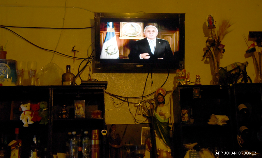 Guatemalan President Otto Perez Molina's live broadcast is seen at a restaurant in Guatemala City on August 23, 2015. President Perez refused to resign August 22nd, hours after he was accused of being a leader of the corruption scandal that has rocked his country, his spokesman said. With just over two weeks to go before general elections, prosecutors and officials from a UN investigative commission said they had uncovered extensive evidence implicating Perez and ex-vice president Roxana Baldetti in a massive, highly organized scheme to reduce importers' customs duties in exchange for bribes.    AFP PHOTO / Johan ORDONEZ