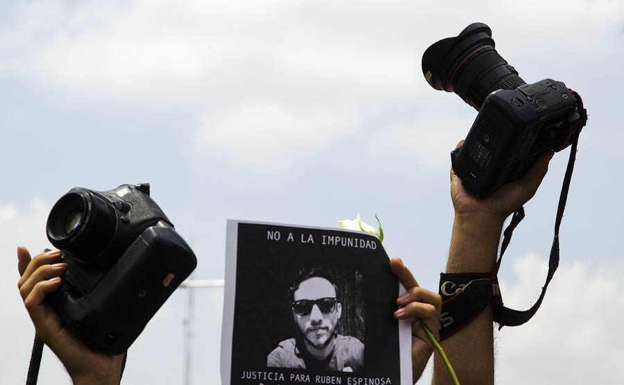 Mexican photojournalists hold a picture of murdered colleague Ruben Espinosa during a demonstration in Guadalajara City, on August 2, 2015. Espinosa was found shot dead on August 1, 2015, in Mexico City, where he had moved two months ago from Veracruz, after reporting strong threats from the government of the state. Since 2010, 11 journalists have been killed and four others have gone missing in Veracruz. AFP PHOTO/HECTOR GUERRERO