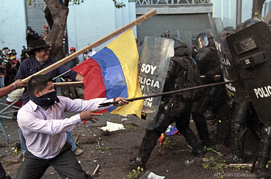 Riot policemen clash with demonstrators in Quito, Ecuador on August 13, 2015, during a strike organized by opposition indigenous groups and unions. Demonstrators took to the streets around Ecuador on Thursday to protest President Rafael Correa's moves to seek a fourth term, but the leftist leader declared that plans for a paralyzing general strike had failed. AFP PHOTO / JUAN CEVALLOS