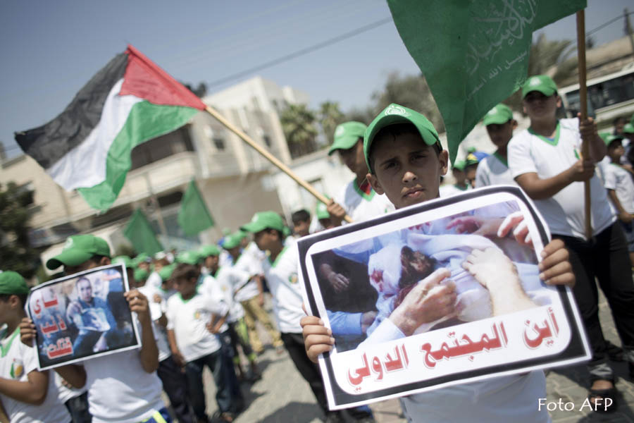 """A Palestinian boy holds a placard showing a picture of a baby and reading in Arabic: """"Where is the international community"""" during a demonstration simulating a funeral ceremony and organised by Palestinian Islamist Hamas supporters in reaction to the death of 18-month-old Ali Saad Dawabsha, the toddler who was burned to death by suspected Jewish extremists, on August 1, 2015 in Khan Yunis in the southern Gaza Strip. The parents and brother of the Palestinian toddler are fighting for their lives, as protests over the arson attack in the occupied West Bank entered a second day.  AFP PHOTO / SAID KHATIB"""