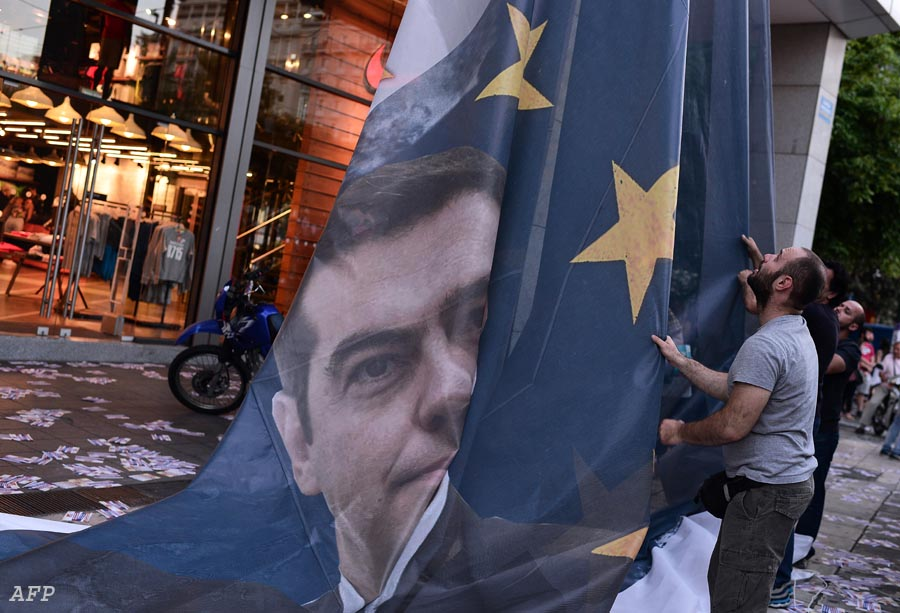 """Protesters take down a huge banner bearing a picture of Greek Prime Minister Alexis Tsipras on a European Union flag from the ministry of finance in Athens as they end the occupation of the building on June 11, 2015. The Greek government on Thursday said it would """"intensify"""" efforts to resolve differences with its EU-IMF creditors to reach a deal that would give the country desperately needed bailout funds. AFP PHOTO / LOUISA GOULIAMAKI"""