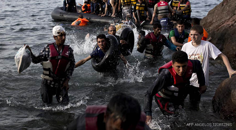 Migrants arrive on the shores of the Greek island of Lesbos after crossing the Aegean Sea from Turkey on a dinghy on September 9, 2015. The EU unveiled plans to take 160,000 refugees from overstretched border states, as the United States said it would accept more Syrians to ease the pressure from the worst migration crisis since World War II. AFP PHOTO / ANGELOS TZORTZINIS