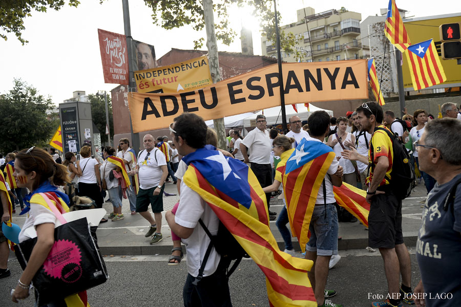 "People with ""Esteladas"" (pro-independence Catalan flag) pass by a banner reading ""Goodbye Spain"" during celebrations of Catalonia's National Day (Diada) which recalls the final defeat of local troops by Spanish king Philip V's forces in 1714, in Barcelona on September 11, 2015. Hundreds of thousands of Catalans were set to pour into the streets today demanding independence, ahead of a regional election billed as an indirect vote on breaking away from Spain.    AFP PHOTO/ JOSEP LAGO"