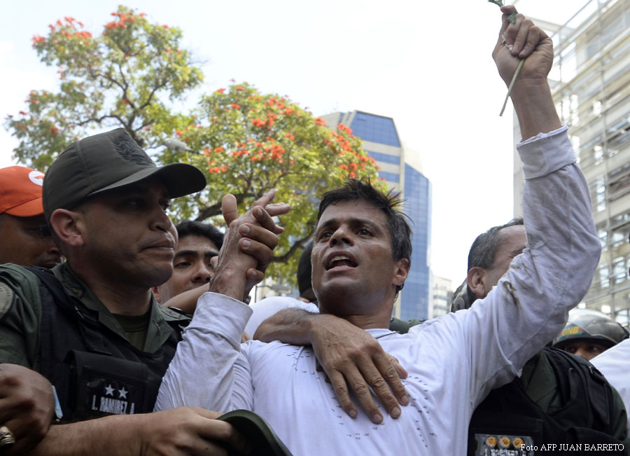 Leopoldo Lopez (R), an ardent opponent of Venezuela's socialist government facing an arrest warrant, is escorted by the National Guard after turning himself in, during a demonstration in Caracas on February 18, 2014. Fugitive Venezuelan opposition leader Lopez turned himself into police Tuesday at a march by thousands of his supporters. Lopez, blamed by President Nicolas Maduro for violent clashes that left three people dead last week, appeared at an anti-government rally in eastern Caracas and quickly surrendered to police.  AFP PHOTO / JUAN BARRETO