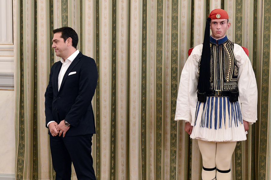 """Greece's leftwing Syriza leader and newly elected Greek Prime Minister Alexis Tsipras (L) stands next to a presidental guard at the presidental palace in Athens, on September 21, 2015, prior to the oath-taking ceremony, a day after the Greek general election. Syriza won 35.5 percent of the vote against 28 percent for conservative New Democracy and is likely to again form a coalition government with the nationalist Independent Greeks (ANEL) party. The EU congratulated Tsipras on his left-wing party's re-election victory and said Greece has """"no time to lose"""" in implementing the reforms agreed as part of its international bailout. AFP PHOTO / LOUISA GOULIAMAKI"""