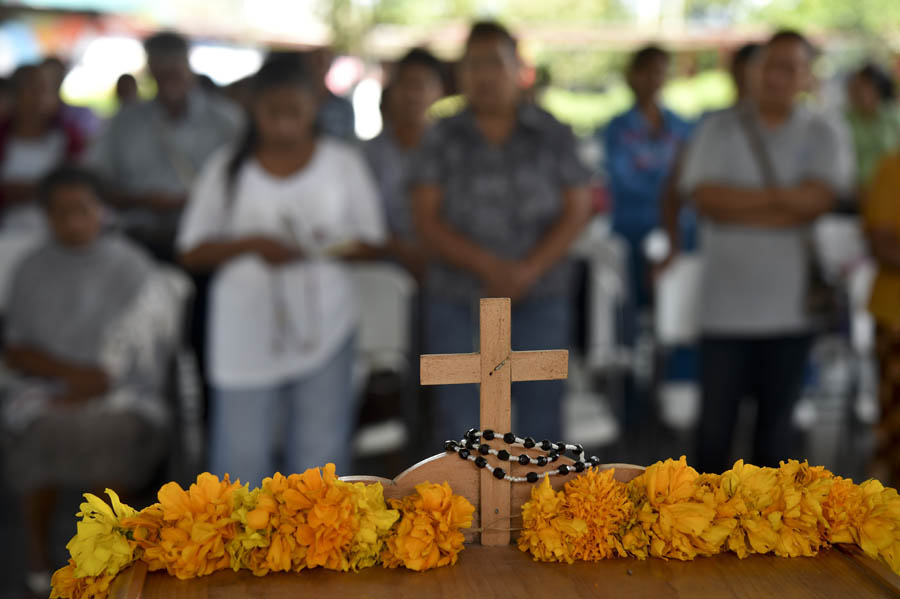 Parents of killed or missing students pray in front of an altar in Ayotzinapa, Mexico on October 6, 2014, Mexico. Authorities discovered over the weekend six adjoining pits containing 28 bodies, some badly burned and in pieces, on a hill outside the Guerrero state city of Iguala, where the students were last seen.     AFP PHOTO/ Yuri CORTEZ
