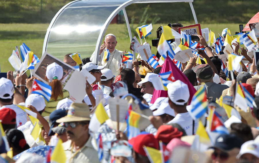 Pope Francis waves at the crowd as he arrives to give a morning mass at the Calixto Garcia square in Holguin, in eastern Cuba, on September 21, 2015. Holguin, a cradle of Catholic faith on the island and also the home region of communist leaders Fidel and Raul Castro, is the only stop on the pope's eight-day, six-city tour of Cuba and the United States that has never received a papal visit.   AFP PHOTO / LUIS ACOSTA
