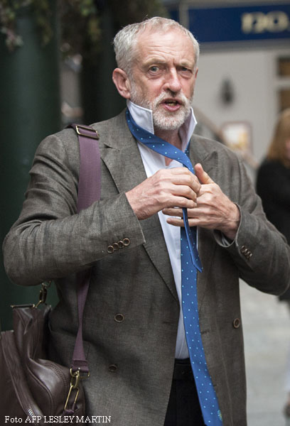 British Labour party leadership contender Jeremy Corbyn poses for pictures with a tie that he was given by a charity worker as he arrives to address a public rally in Glasgow, Scotland, on August 14, 2015. Voting began Friday to elect the new leader of Britain's main opposition Labour party, with Jeremy Corbyn, a veteran socialist who would move the party significantly to the left, favourite to win.  AFP PHOTO / LESLEY MARTIN
