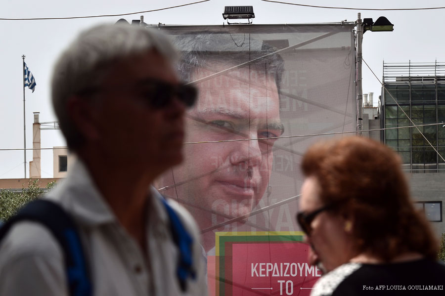 People walk past a pre-election poster of the leader of the Greece's radical-left Syriza party, Alexis Tsipras, in central Athens on September 7, 2015, ahead of upcoming snap parliamentary elections on September 20. An opinion poll suggests that Greece's former governing radical left party has dropped marginally behind the main opposition conservatives in popularity, for the first time since it gained power in January 2015. AFP PHOTO/ LOUISA GOULIAMAKI