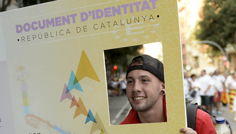 A man poses with a giant fake Catalan ID card during celebrations of Catalonia's National Day (Diada) which recalls the final defeat of local troops by Spanish king Philip V's forces in 1714, in Barcelona on September 11, 2015. Hundreds of thousands of Catalans were set to pour into the streets today demanding independence, ahead of a regional election billed as an indirect vote on breaking away from Spain.    AFP PHOTO/ JOSEP LAGO