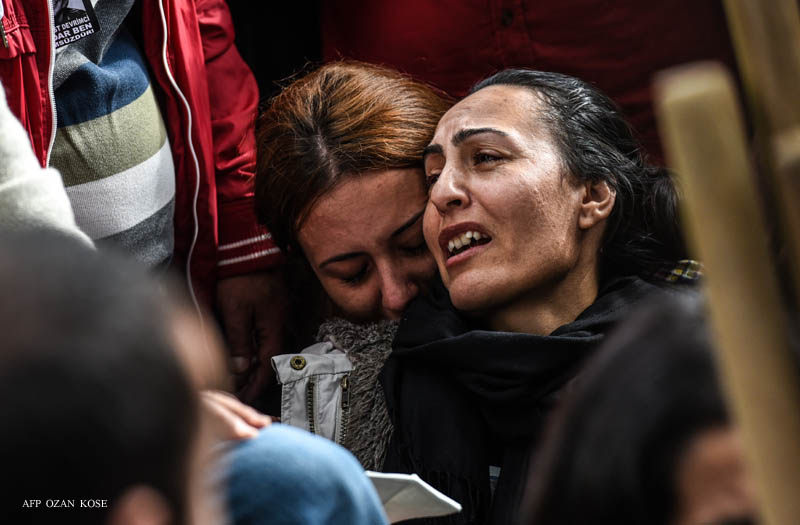 Relatives mourn near the grave of Serdar Ben, a victim of the twin bombings in Ankara, duringhisfuneral in Istanbul on October 15, 2015. Turkey woke in mourning on October 11 after at least 99 people were killed by suspected suicide bombers at a peace rally of leftist and pro-Kurdish activists in Ankara, the deadliest such attack in the country's recent history. AFP PHOTO / OZAN KOSE
