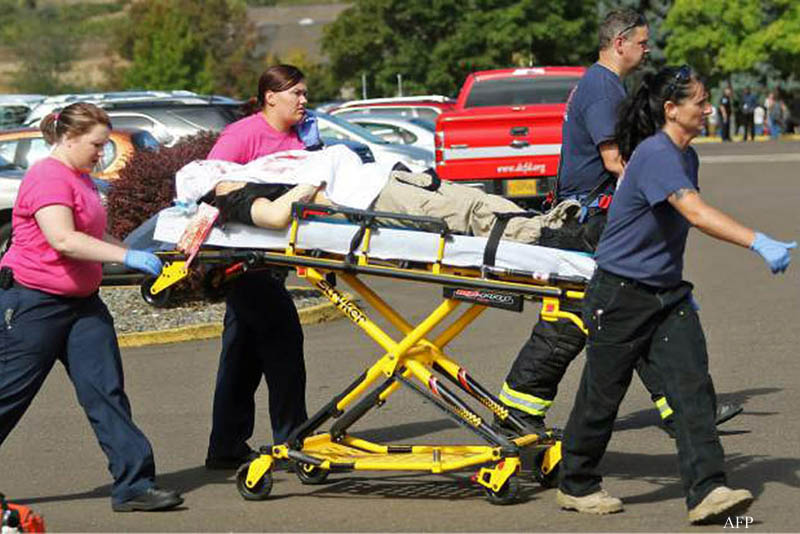 """Authorities move a shooting victim after a gunman opened fire at Umpqua Community College in Roseburg, Oregon, on October 1, 2015. Local media have quoted Oregon State Police Lieutenant Bill Fugate as saying between seven and 10 people were killed and at least 20 injured. A 20-year-old shooter has been confirmed dead after a shoot-out with police, officials said.   = RESTRICTED TO EDITORIAL USE - MANDATORY CREDIT """"AFP PHOTO / Michael Sullivan / The News-Review"""" - NO MARKETING NO ADVERTISING CAMPAIGNS - DISTRIBUTED AS A SERVICE TO CLIENTS ="""