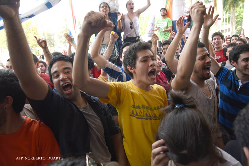 Paraguayan university students surround and prevent from leaving the university compound 37 members of the Supreme Council and some 30 staffers at the National University in Asuncion, on September 22, 2015. About 2,000 students gathered in front of the rector's office demanding the resignation of rector Froilan Pereira, accusing him of corruption and nepotism. AFP PHOTO/ NORBERTO DUARTE