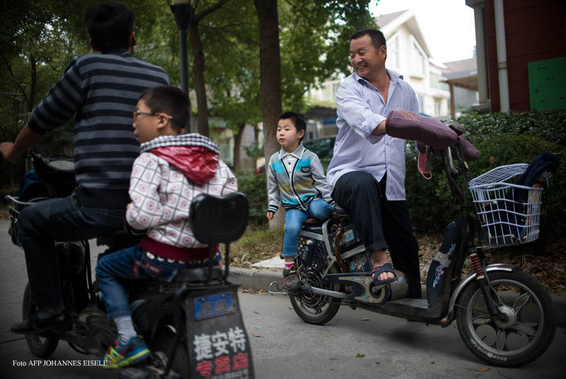 This picture taken on October 27, 2014 shows six-year-old Pan Yulin (C), sitting on his uncle's scooter as they arrive at a school for migrant children, which has been shut down recently by authorities in Shanghai's Baoshan district. China has complex residency laws and where most migrant workers remain registered in their native towns or villages, they do not qualify for the all-important hukou, or household registration permit in the city where they live. Without this document their children do not qualify for places in public schools, making the illegal fee-paying migrant schools their only option.  CHINA OUT  AFP PHOTO / JOHANNES EISELE