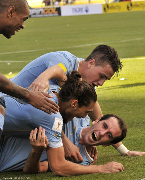 Uruguay's defender Diego Godin (bottom) celebrates with defenders Martin Caceres (L) and Jose Maria Gimenez after scoring against Bolivia during the Russia 2018 FIFA World Cup qualifiers match, at the Hernando Siles stadium in La Paz, on October 8, 2015. AFP PHOTO / AIZAR RALDES