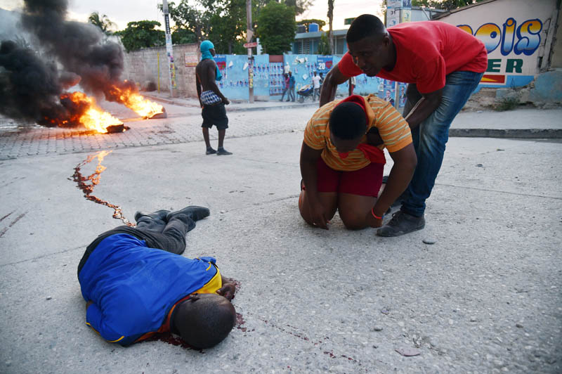 TOPSHOTS A supporter of presidential candidate Moise Jean Charles, shot dead minutes after the Provisional Electoral Council(CEP) gave the results of the first round of presidential elections, lies on the ground as other supporters gather around during a demonstration in Delmas 33, in Port-au-Prince, on November 5, 2015. Haiti's presidential election will go to a runoff between ruling party candidate Jovenel Moise and Jude Celestin, close to former president Rene Preval, officials said. AFP PHOTO/HECTOR RETAMAL