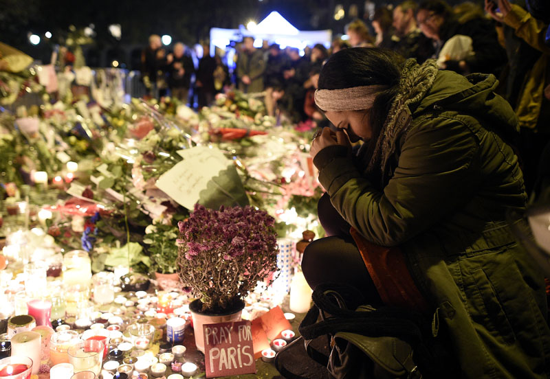A woman prays at a makeshift memorial in front of the Bataclan theatre, one of the site of the attacks in Paris, on November 15, 2015, in Paris. Islamic State jihadists claimed a series of coordinated attacks by gunmen and suicide bombers in Paris that killed at least 132 people in scenes of carnage at a concert hall, restaurants and the national stadium.AFP PHOTO / FRANCK FIFE / AFP / FRANCK FIFE