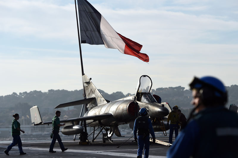 A French flag flies above French naval technicians working on the flight deck of the aircraft carrier Charles-de-Gaulle at a military port in the southern French city of Toulon, on November 18, 2015, before leaving in Eastern Mediterranean Sea. France said its Charles de Gaulle aircraft carrier would be deployed to the eastern Mediterranean to boost operations in Syria as Paris intensifies a bombing campaign against the Islamic State group there. The latest move follows attacks in the French capital, claimed by the jihadist group, which left 129 people dead and hundreds more wounded. AFP PHOTO / ANNE-CHRISTINE POUJOULAT / AFP / ANNE-CHRISTINE POUJOULAT