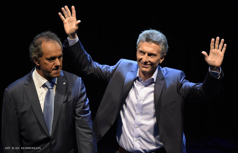 "The Head of Government of the Autonomous City of Buenos Aires and presidential candidate for the ""Cambiemos"" (Let's Change) party Mauricio Macri (R) waves next to Buenos Aires province governor and presidential candidate of the ""Frente para la Victoria"" (Front for Victory) Daniel Scioli (L) after a debate in Buenos Aires on November 15, 2015, ahead of next November 22 run-off election. AFP PHOTO / Juan Mabromata / AFP / JUAN MABROMATA"