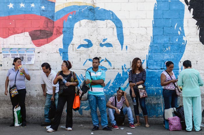 """People line up in front of a propaganda graffiti depicting late Venezuelan President (1999-2013) Hugo Chavez (L),  on a wall of the Petare shantytown in Caracas on December 1 , 2015. Sixteen years into late president Hugo Chavez's leftist """"revolution,"""" opinion polls indicate the opposition is poised to win legislative elections Sunday for the first time since the firebrand leader came to power.  AFP PHOTO/FEDERICO PARRA / AFP / FEDERICO PARRA"""
