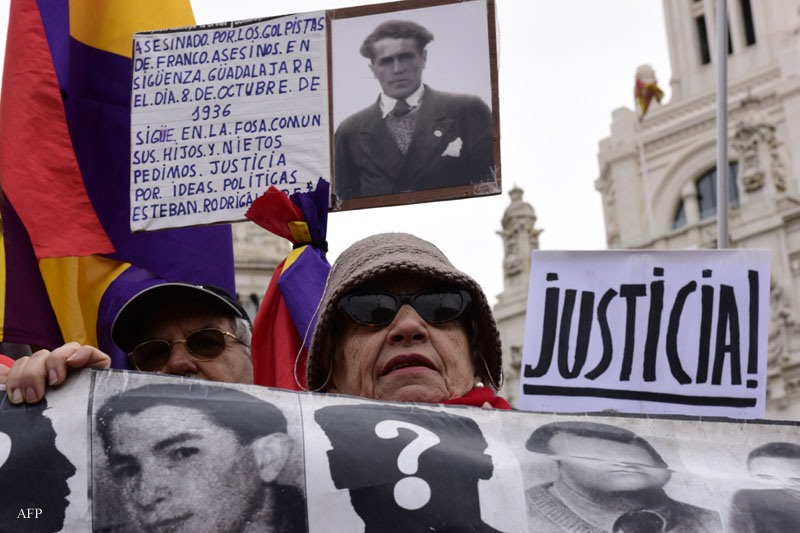 Demonstrators show photographs of Francoism victims during a demonstration in favour of Historical Memory in Madrid on November 22, 2015. Franco came to power after his side won Spain's 1936-39 civil war with the help of Germany's Adolph Hitler and Italy's Benito Mussolini. He then ruled Spain with an iron fist until his death on November 20, 1975. Forty years after the death of Francisco Franco, historians still work to demolish myths that the Spanish dictator spun about himself to hold on to power for decades. AFP PHOTO / JAVIER SORIANO / AFP / JAVIER SORIANO