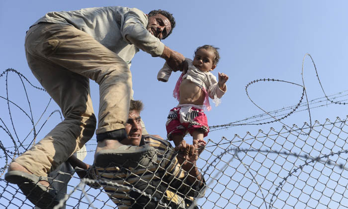 "A Syrian child fleeing the war is lifted over border fences to enter Turkish territory illegally, near the Turkish border crossing at Akcakale in Sanliurfa province on June 14, 2015. Turkey said it was taking measures to limit the flow of Syrian refugees onto its territory after an influx of thousands more over the last days due to fighting between Kurds and jihadists. Under an ""open-door"" policy, Turkey has taken in 1.8 million Syrian refugees since the conflict in Syria erupted in 2011. AFP PHOTO / BULENT KILIC"