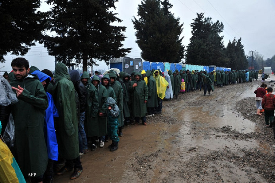"Migrants and refugees wait for food at the Greek-Macedonian border near the Greek village of Idomeni on March 9, 2016, where thousands of refugees and migrants are trapped by the Balkan border blockade.  The Balkan trail from Greece to northern Europe used by floods of migrants was blocked on March 9 after a string of nations slammed shut their borders, hiking pressure on the EU and Turkey to nail down a ""game-changing"" grand bargain. / AFP / SAKIS MITROLIDIS"