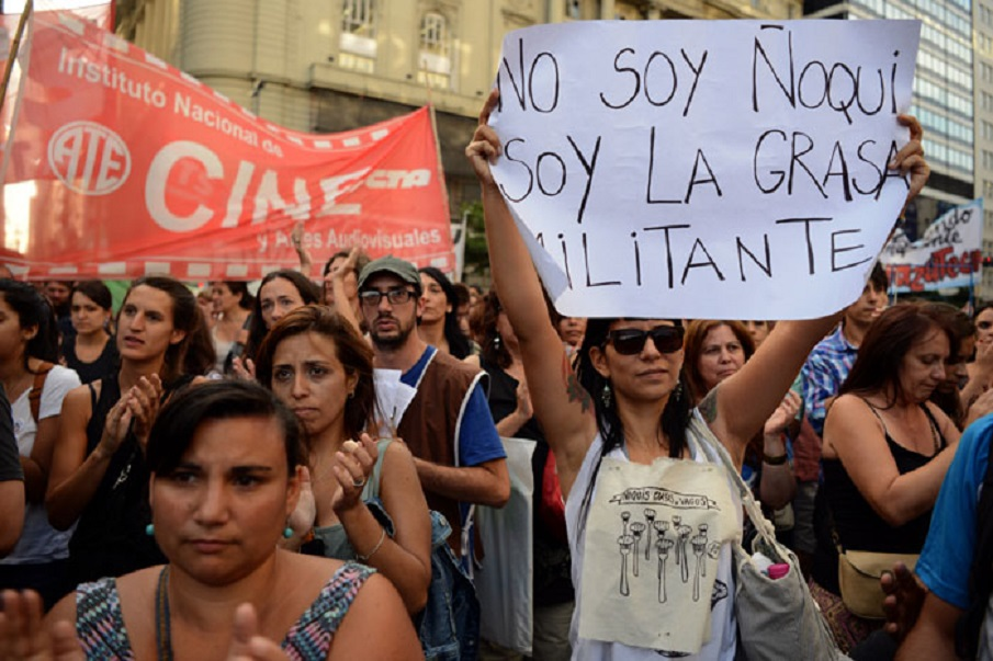 """A woman holds a sign reading """"I am not gnocchi, I am the vulgar activist"""" as former employees of the Kirchner Cultural Centre (CCK) protest against the massive firing of civil servants by the government of Argentinian President Mauricio Macri outside the CCF building in Buenos Aires, on January 29, 2016. The word """"gnocchi"""" is used in Argentinian slang to define employees who don't really work but still have a salary. AFP PHOTO/EITAN ABRAMOVICH / AFP / EITAN ABRAMOVICH"""