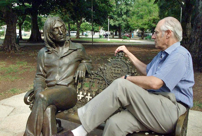Sir George Martin (R), known world-wide as the fifth Beatle from his collaborations with the famous musical group, shares a seat with a statue of John Lennon in a park of Havana, Cuba, 30 October 2002. Martin made a visit to Cuba to offer conferences on the Beatles and to participate in concerts with Cuban musicians.            AFP PHOTO/Adalberto ROQUE / AFP / ADALBERTO ROQUE